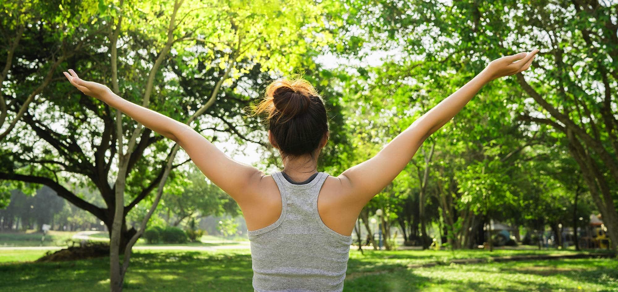 Eine sportliche Frau breitet voller Energie und gestärkt ihre Arme aus